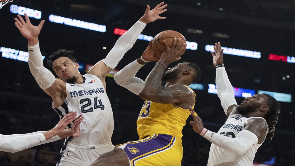 Los Angeles Lakers forward LeBron James, centre, looks to shoot under pressure from Memphis Grizzlies guard Dillon Brooks, left, and forward Jae Crowder during the second half of an NBA basketball game in Los Angeles, Tuesday, Oct. 29, 2019. (AP Photo/Kyusung Gong).