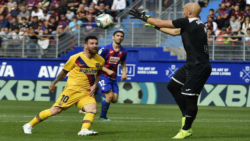 Barcelona's Lionel Messi, left, tries to beat Eibar's goalkeeper Marko Dmitrovic during a Spanish La Liga football match at the Ipurua stadium in Eibar, Spain, Saturday Oct. 19, 2019. (AP Photo/Alvaro Barrientos).