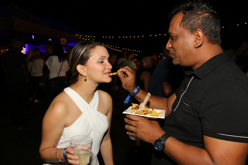 Restaurateur Horace Colahar helps Gastroenterologist Yadira Borrero Vaz to a serving of Holy Mole Pork Nachos from Pink Apron.