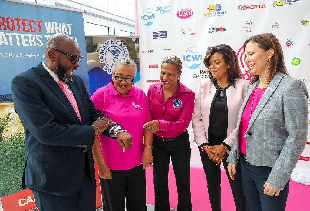 Reverend Astor Carlyle (left) of Webster United Church and his pink wrist band have the attention of these ladies during the launch of the 2019 ICWI Pink Run held on Tuesday, September 24 at Toyota Jamaica's Old Hope Road branch. Looking on are: (l-r) Carolind Graham, Chairman, Jamaica Reach to Recovery; Danielle Cunningham, Beverage Marketing Manager, LASCO Distributors; Yulit Gordon, Executive Director, Jamaica Cancer Society and Samantha Samuda, Vice President, Marketing and Human Resources, ICWI.