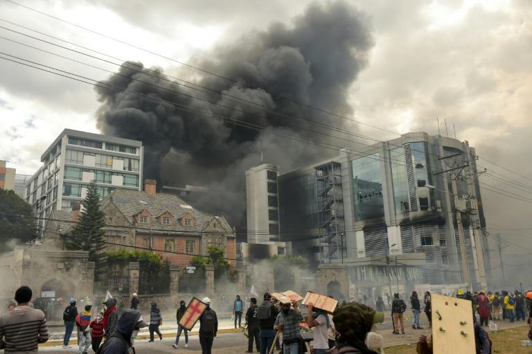Des manifestants encagoulés mettent le feu au bureau de l'Inspection générale des finances, dans le nord de Quito, le 12 octobre 2019
