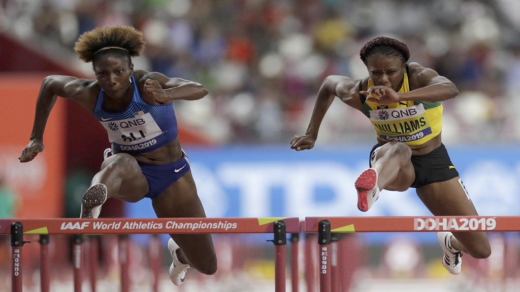 Danielle Williams, of Jamaica and Nia Ali, of the United States compete in a women's 100m hurdles semifinal at the World Athletics Championships in Doha, Qatar, Sunday, Oct. 6, 2019. (AP Photo/Petr David Josek).
