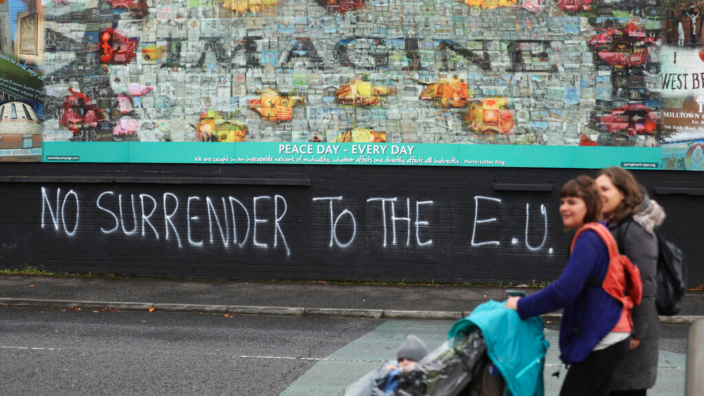 In this photo dated October 14, 2019 people walk past pro-Brexit graffiti in West Belfast Northern Ireland. Fears about a return to the violence that killed more than 3,500 people over three decades have made Northern Ireland the biggest hurdle for U.K. and EU officials who are trying to hammer out a Brexit divorce deal. (AP Photo/Peter Morrison)