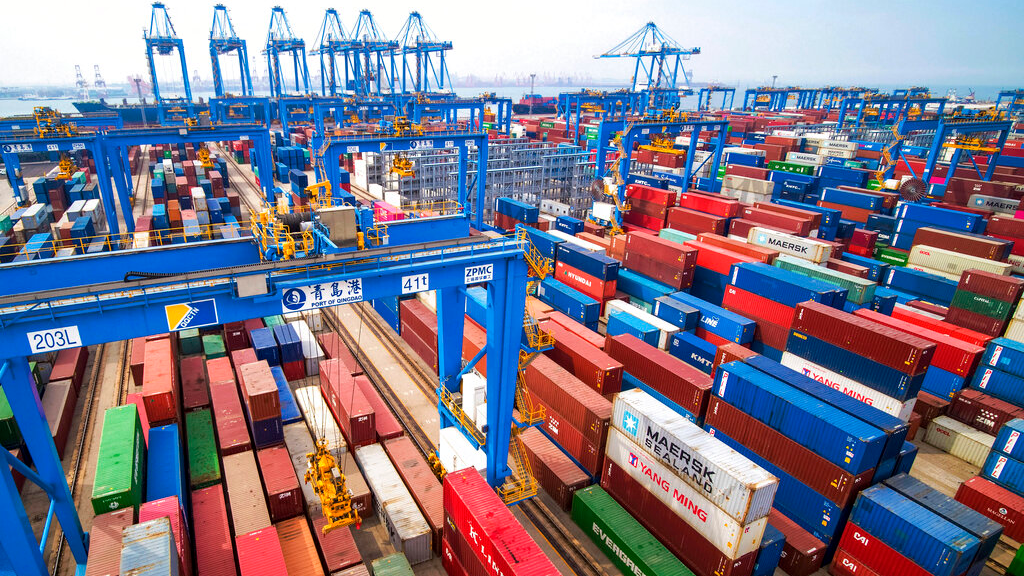 In this Tuesday, May 14, 2019, photo, containers are piled up at a port in Qingdao in east China's Shandong province. China's imports from the United States plunged 31.4% in June from a year earlier amid a tariff war with Washington, while exports to the U.S. market sank 7.8%, Customs data showed Friday, July 12, 2019. (Chinatopix via AP)