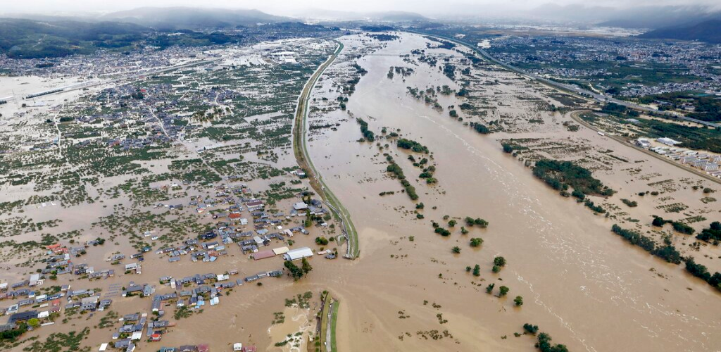 Residential area, left, are submerged in muddy waters after an embankment of the Chikuma River broke because of Typhoon Hagibis, in Nagano, central Japan, Sunday, Oct. 13, 2019.