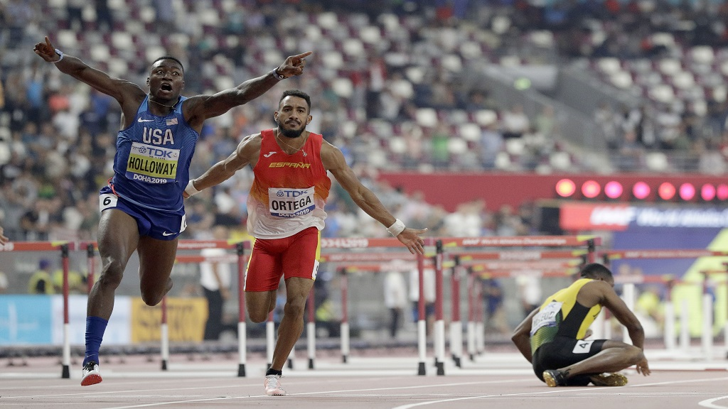 Grant Holloway, of the United States celebrates as he wins the gold medal in the men's 110m hurdles final at the World Athletics Championships in Doha, Qatar, Wednesday, Oct. 2, 2019.  At center is Orlando Ortega, of Spain and at right is Omar McLeod, of Jamaica who fell. (AP Photo/Petr David Josek).