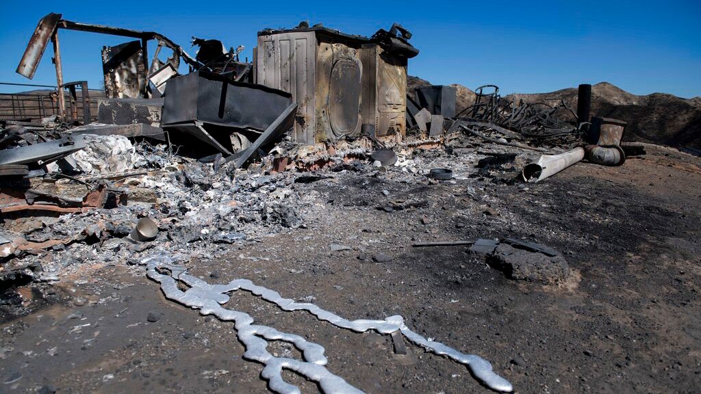 Debris from a hilltop home smolders after being burned by the Tick Fire, October 25, 2019, in Santa Clarita, California. (AP Photo/ Christian Monterrosa)