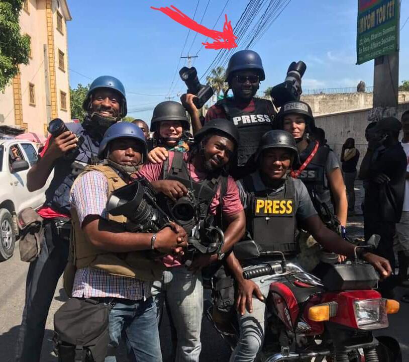 Debout sur une motocyclette, Dieu-Nalio Chery, deux (2) caméras en mains, est entouré de ses confrères, pour une prise de photo.