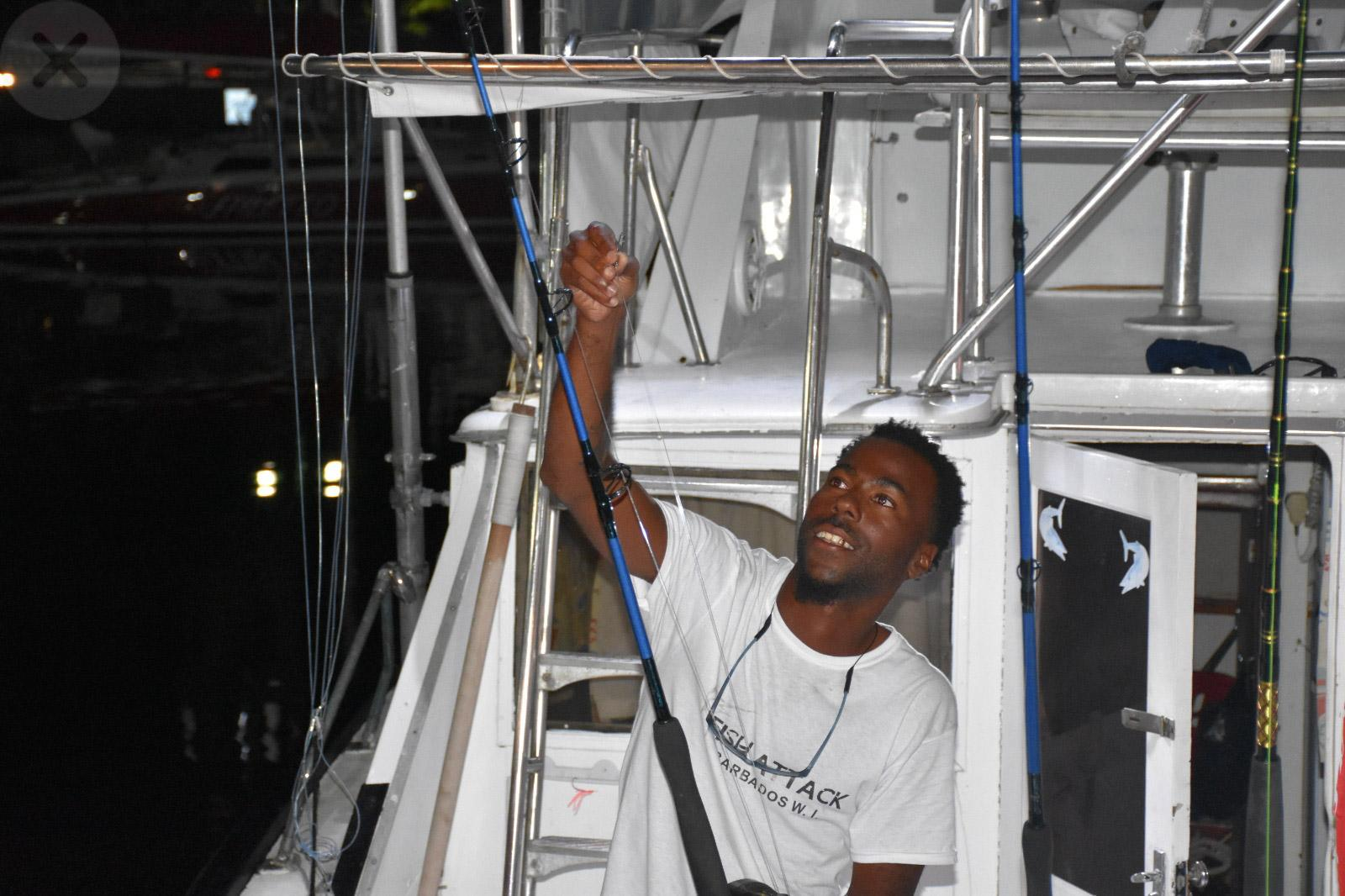 First Mate Mario checks the lines and rods aboard Fish Attack ahead of day two of  2019 Brian Manning Memorial Cup hosted by the Barbados Game Fishing Association,