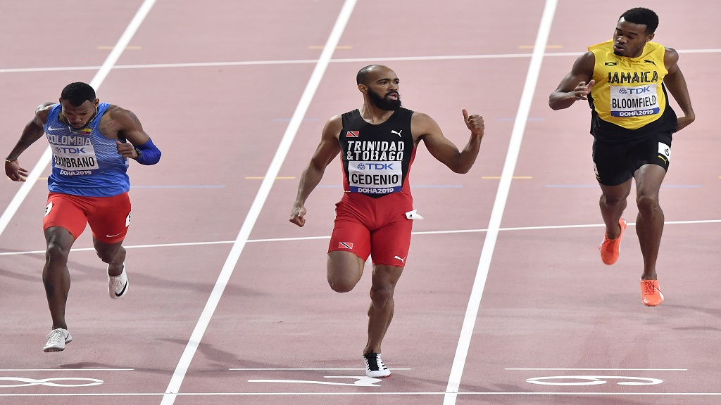 Machel Cedenio, of Trinidad And Tobago, flashes a thumbs up as he crosses the finish line ahead of Anthony José Zambrano, of Colombia, left, and Akeem Bloomfield, of Jamaica, during the men's 400m semifinal at the World Athletics Championships in Doha, Qatar, Wednesday, Oct. 2, 2019. (AP Photo/Martin Meissner).