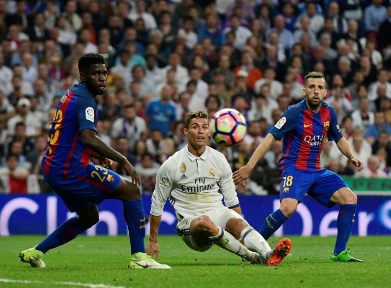 L'attaquant du Real Madrid Cristiano Ronaldo (c) à la lutte avec le défenseur du Barça Samuel Umtiti (g) lors du Clasico, au stade Santiago Bernabeu, le 23 avril 2017