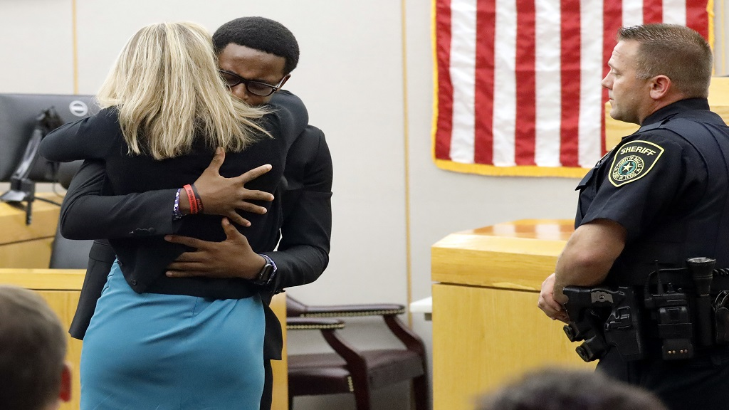 Botham Jean's younger brother Brandt Jean hugs convicted murderer and former Dallas Police Officer Amber Guyger after delivering his impact statement to her after she was sentenced to 10 years in jail, Wednesday, Oct. 2, 2019, in Dallas. (Tom Fox/The Dallas Morning News via AP, Pool)