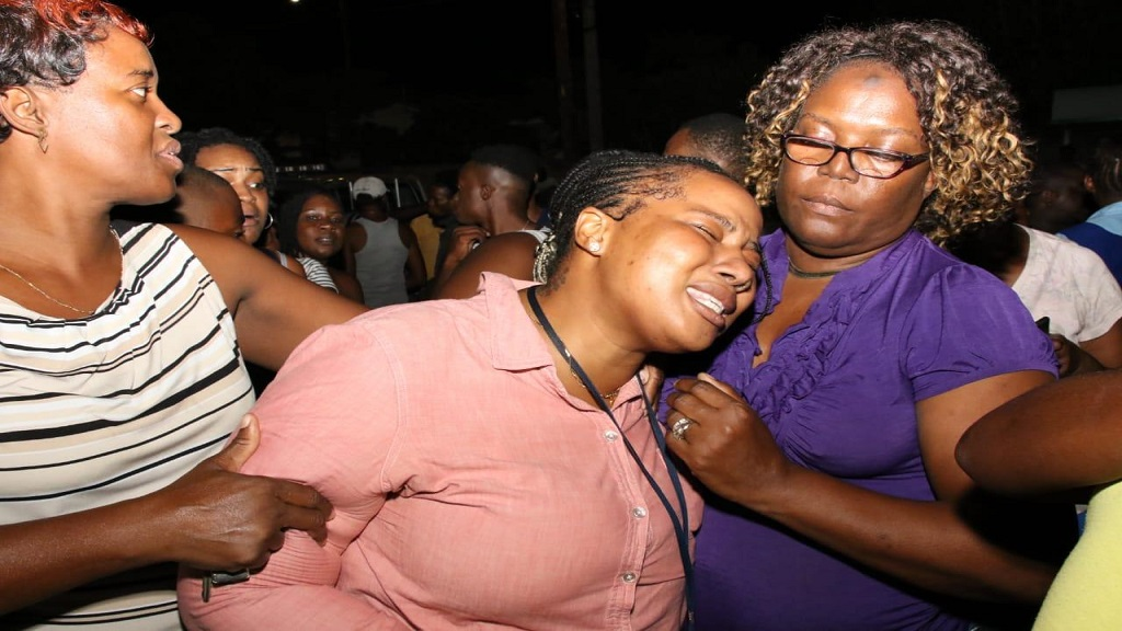 A relative of one of the students who were seriously injured in a freak accident at Clan Carthy Primary School in Kingston on Monday afternoon being calmed amid her state of extreme grief. (Photo: Marlon Reid)