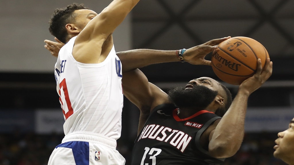 Los Angeles Clippers shooting guard Amir Coffey (7) challenges Houston Rockets shooting guard James Harden (13) during the second quarter of an NBA preseason basketball game, Thursday, Oct 3, 2019, in Honolulu. (AP Photo/Marco Garcia).
