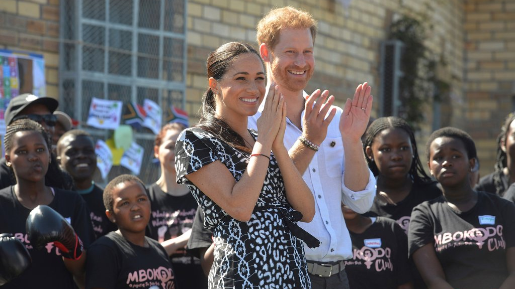 In this Monday, Sept, 23, 2019 file photo, Britain's Prince Harry and Meghan, Duchess of Sussex greet youths on a visit to the Nyanga Methodist Church in Cape Town, South Africa, which houses a project where children are taught about their rights, self-awareness and safety, and are provided self-defence classes and female empowerment training to young girls in the community. (Courtney Africa/Pool via AP, File)
