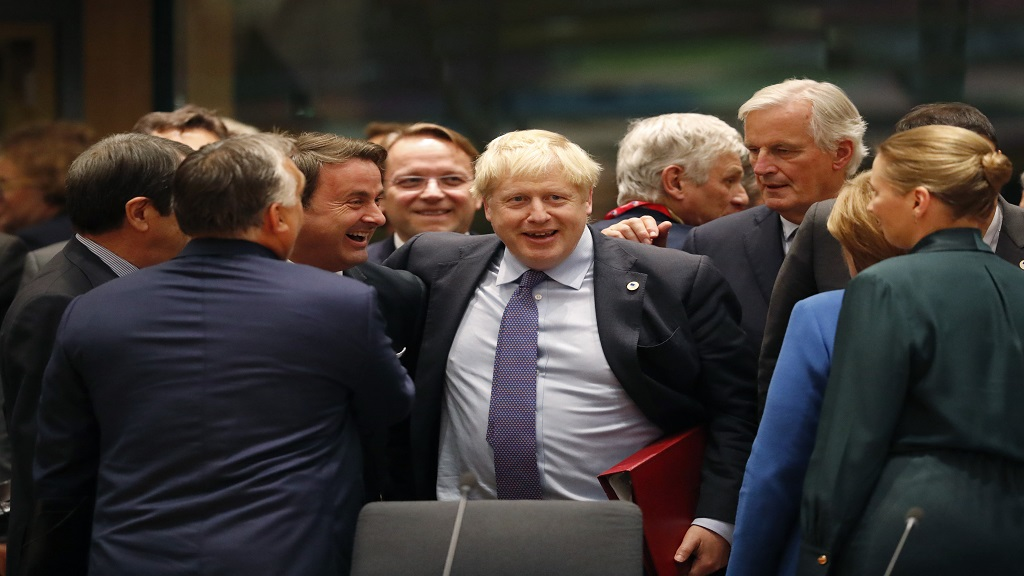 British Prime Minister Boris Johnson, centre, is greeted by Luxembourg's Prime Minister Xavier Bettel, centre left, during a round table meeting at an EU summit in Brussels, Thursday, Oct. 17, 2019. Britain and the European Union reached a new tentative Brexit deal on Thursday, hoping to finally escape the acrimony, divisions and frustration of their three-year divorce battle. (AP Photo/Frank Augstein).