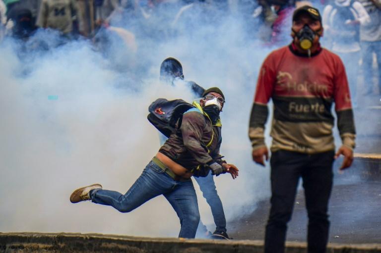 Un manifestant renvoie une cartouche de gaz lacrymogène pendant une manifestation à Quito, en Equateur, le 11 octobre 2019
