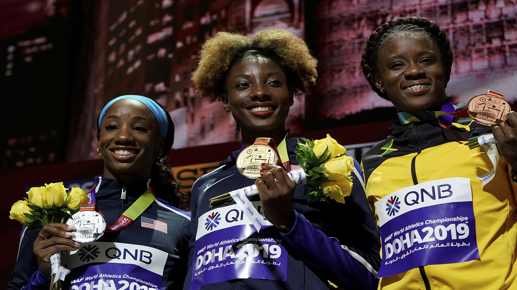 From right,  bronze medallist Danielle Williams of Jamaica and the U.S. pair of gold medallist Nia Ali and silver medallist Kendra Harrison display their medals for the women's 100m hurdles at the World Athletics Championships in Doha, Qatar, Sunday, Oct. 6, 2019. (AP Photo/Morry Gash).