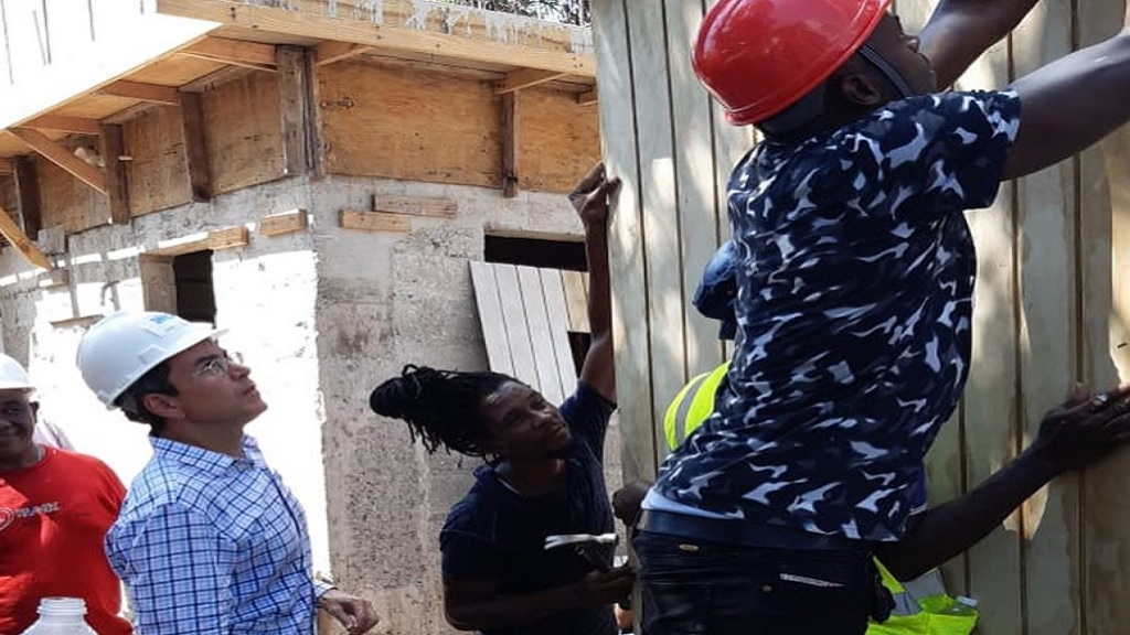 Sprint legend Usain Bolt helps to build a home for St Catherine resident Sean Sutherland, who lost his dwelling in a fire in July.