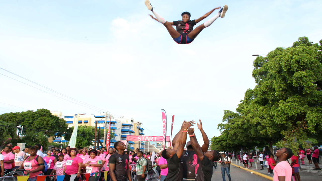 A cheerleader is hoisted in the air during the ICWI Pink Run at Emancipation Park on Sunday.