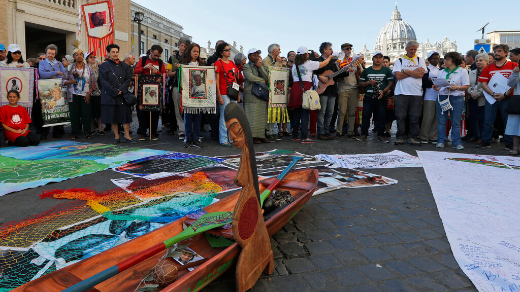 In this photo taken on October 19, 2019, members of Amazon indigenous populations prepare for a a Via Crucis (Way of the Cross) procession from St. Angelo Castle to the Vatican. In foreground is a wooden statue portraying a naked pregnant woman. (AP Photo/Andrew Medichini)