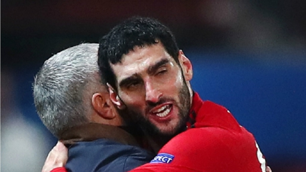 Marouane Fellaini embraces Jose Mourinho.