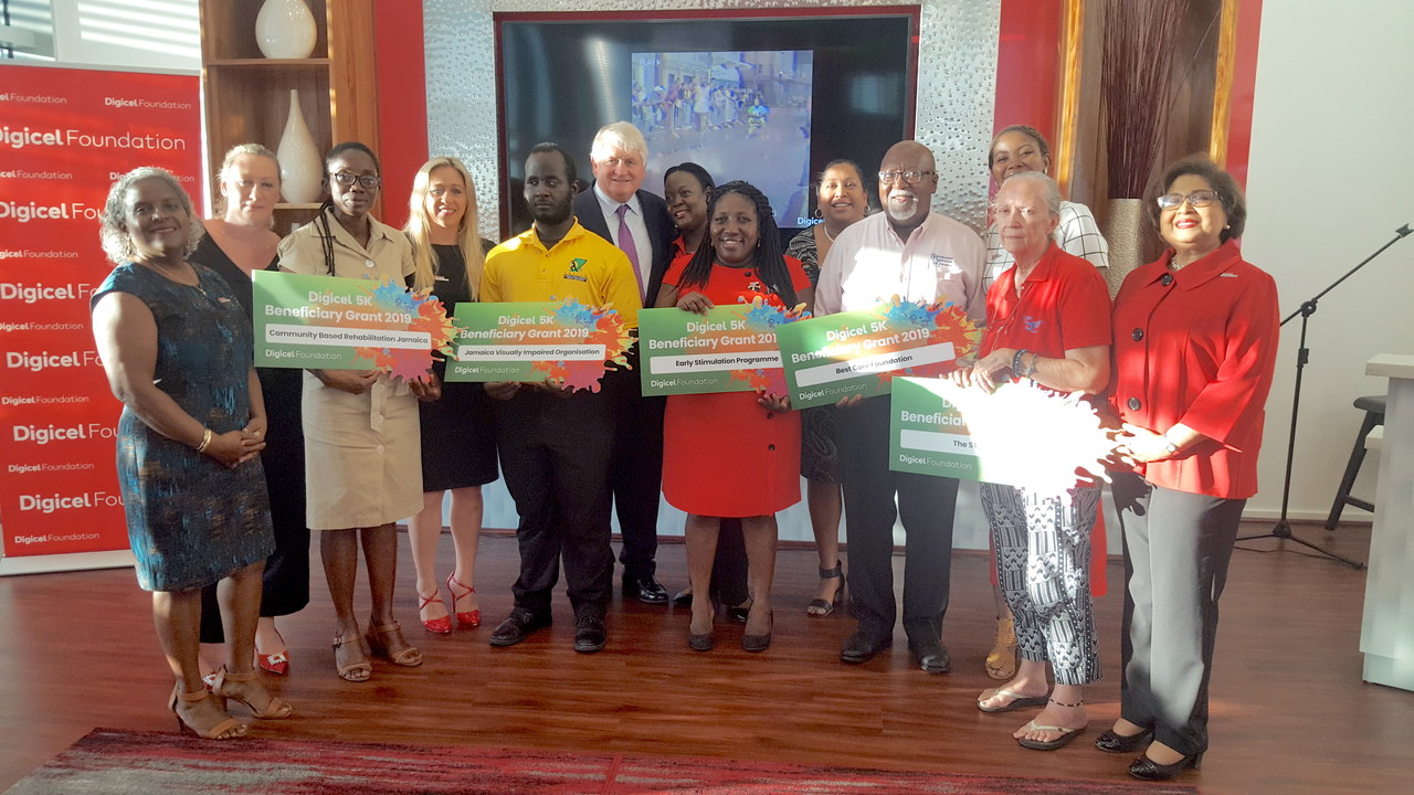 Digicel 5k beneficiaries pose with Digicel representatives - including chairman Denis O'Brien - and their symbolic cheques at a handover ceremony at the Digicel headquarters on Monday.