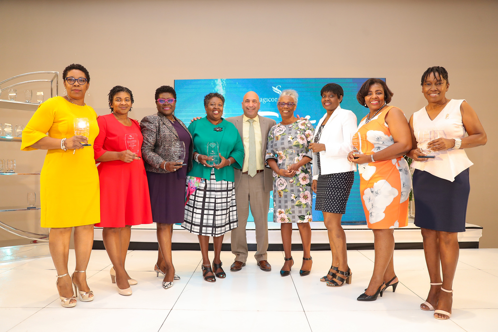 Christopher Zacca (centre), President and CEO, Sagicor Group Jamaica, embraces Sagicor team members honoured with Long Service Awards for between 30 and 40 years of service to the company, during a ceremony at the AC Marriott Hotel recently. From left are: Dahlia Allen Palmer, Sheryl Dacres, Janice Grant Taffe, Curlinea Spence, Jacinth Kelly, Pamela Leith, Yasmin Perry and Erica Prendergast.