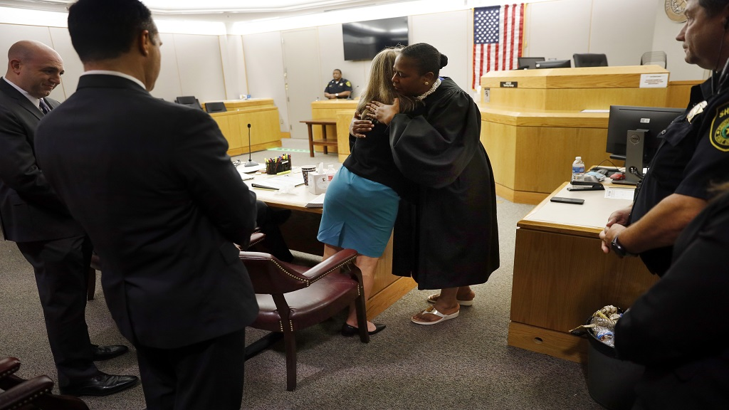 Former Dallas Police Officer Amber Guyger gives State District Judge Tammy Kemp a hug after the judge had given her a Bible and before Guyger left for jail, Wednesday, Oct. 2, 2019, in Dallas. (Tom Fox/The Dallas Morning News via AP, Pool)