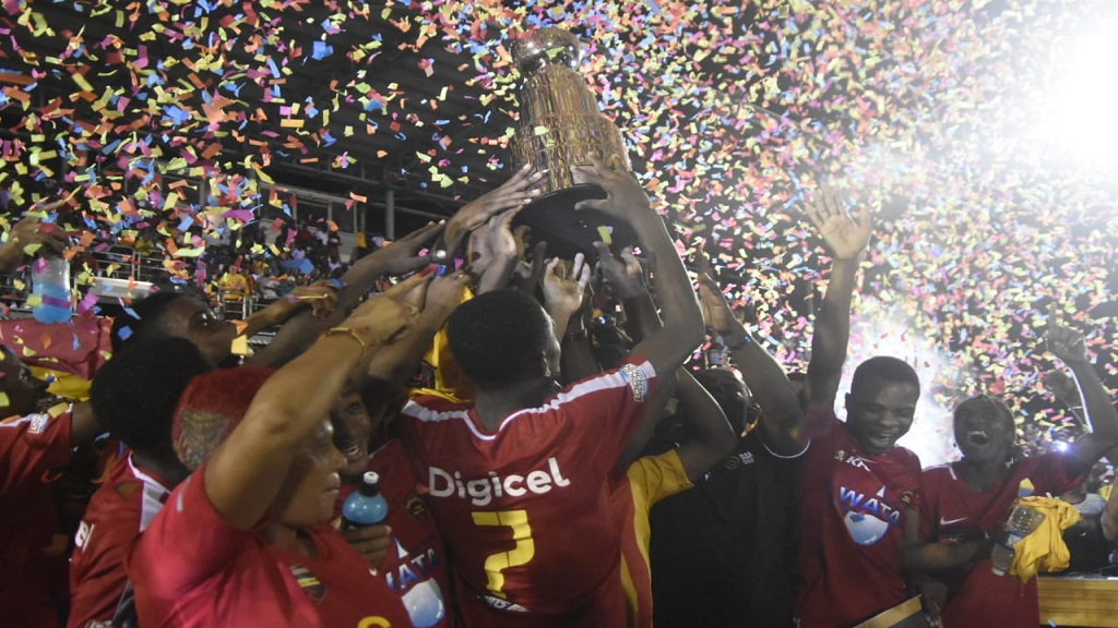 Cornwall College's players hoist the Champions Cup in celebration after defeating Jamaica College 1-0 in the final on Saturday night at the Montego Bay Sports Complex. (PHOTOS: Marlon Reid).