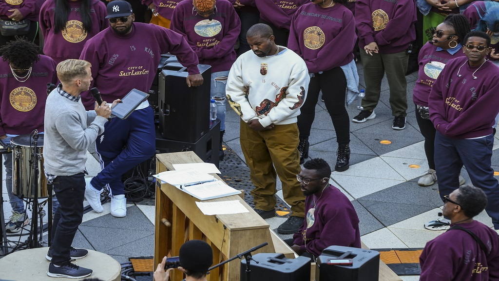 "Kanye West (centre) bows his head in prayer during his ""Sunday Service"" at The Gateway in Salt Lake City on Saturday, October 5, 2019. Thousands packed into the outdoor mall, causing people to stand on and climb up anything they could find to catch a glimpse of West. (Colter Peterson/The Deseret News via AP)"