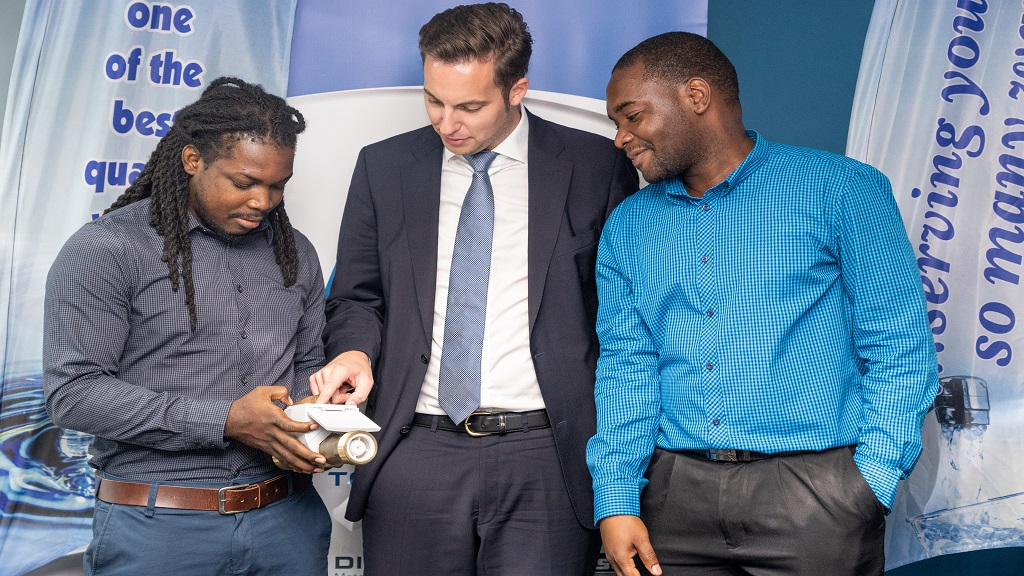 - Stefan Raeder (center), Regional Manager at Deihl Metering, examines a sample of a HYDRUS Smart Water Meter with Shanroy Dennis (left) and Kevoy Smith, both Engineering Masters students at UTECH during an executive meeting, held recently at the NWC corporate office.