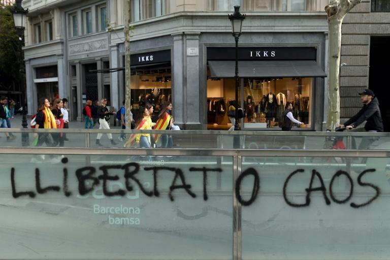 """Des jeunes drapés dans des drapeaux catalans passent devant un graffiti """"Liberté ou Chaos"""" après une nouvelle nuit de violences, le 18 octobre 2019 à Barcelone"""