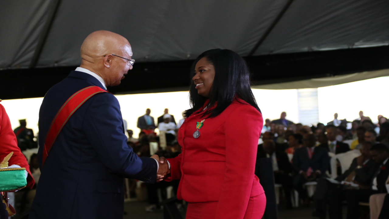 Tamar Blake receives the Badge of Honour for Gallantry from Governor General Sir Patrick Allen at King's House on Monday.
