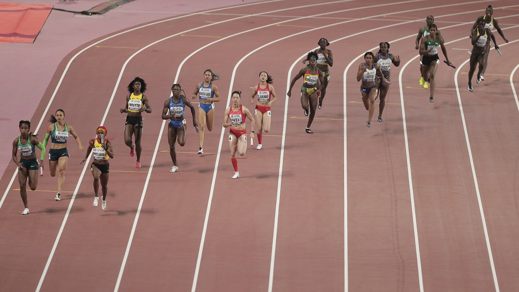 Competitors race in heat one of the women's 4x100 metre relay semifinals at the World Athletics Championships in Doha, Qatar, Friday, Oct. 4, 2019. (AP Photo/Nariman El-Mofty).