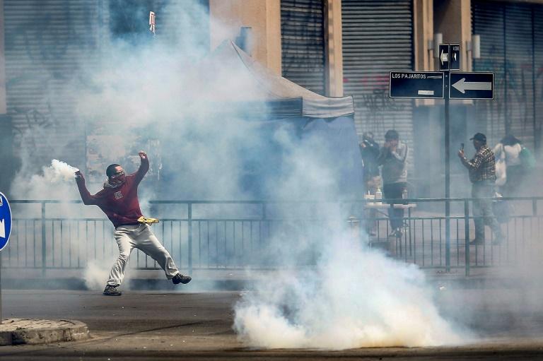 Un manifestant renvoie une grenade lacrymogène vers les forces de l'ordre, lors de manifestations le 19 octobre 2019 à Santiago du Chili