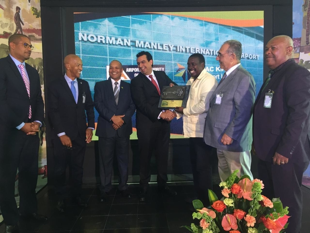 Minister of Transport and Works Robert Montague (third right) joins Raúl Revuelta (centre), CEO of GAP and other officials at the official handover at the Norman Manley International Airport in Kingston.