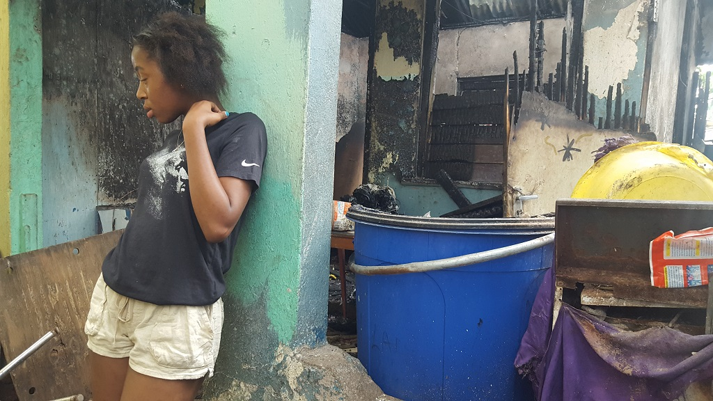 A distraught looking Andrica Morris, a 14-year-old Papine High School student, at her Grants Pen home in St Andrew which was gutted by fire on Friday.