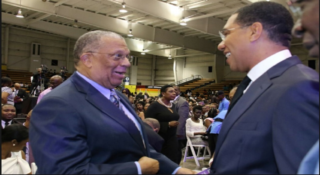 Opposition Leader, Dr Peter Phillips (left), and Prime Minister Andrew Holness exchange pleasantries during a formal event that both attended.