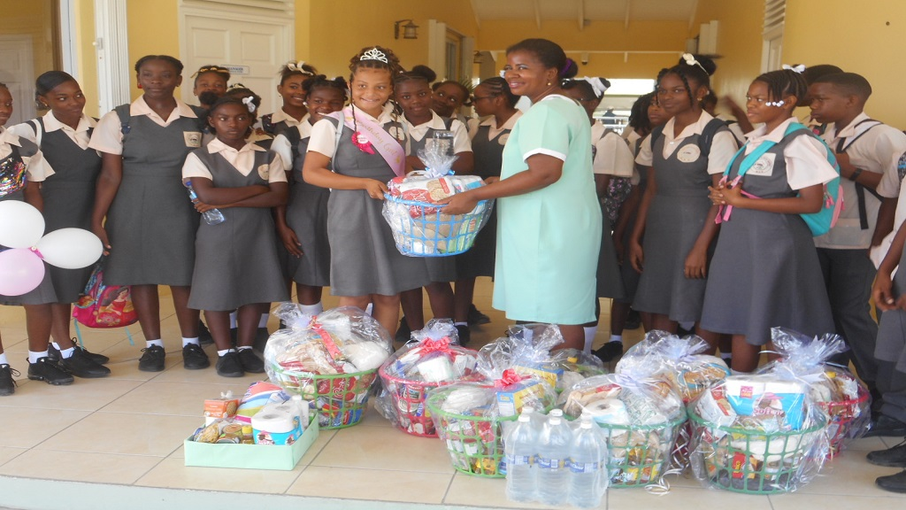 A student of Micoud Secondary School presenting Comfort Bay Senior Citizens Home with hampers