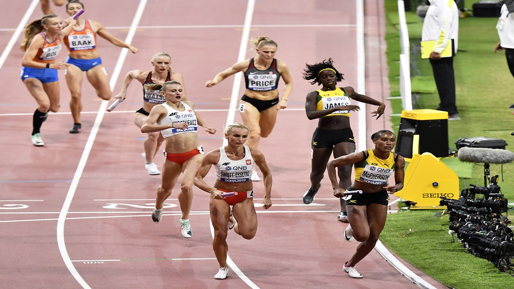 Stephenie Ann McPherson of Jamaica, right, and Justyna Swiety-Ersetic of Poland lead their heat of the women's 4x400m relay during the World Athletics Championships in Doha, Qatar, Saturday, Oct. 5, 2019. (AP Photo/Martin Meissner).