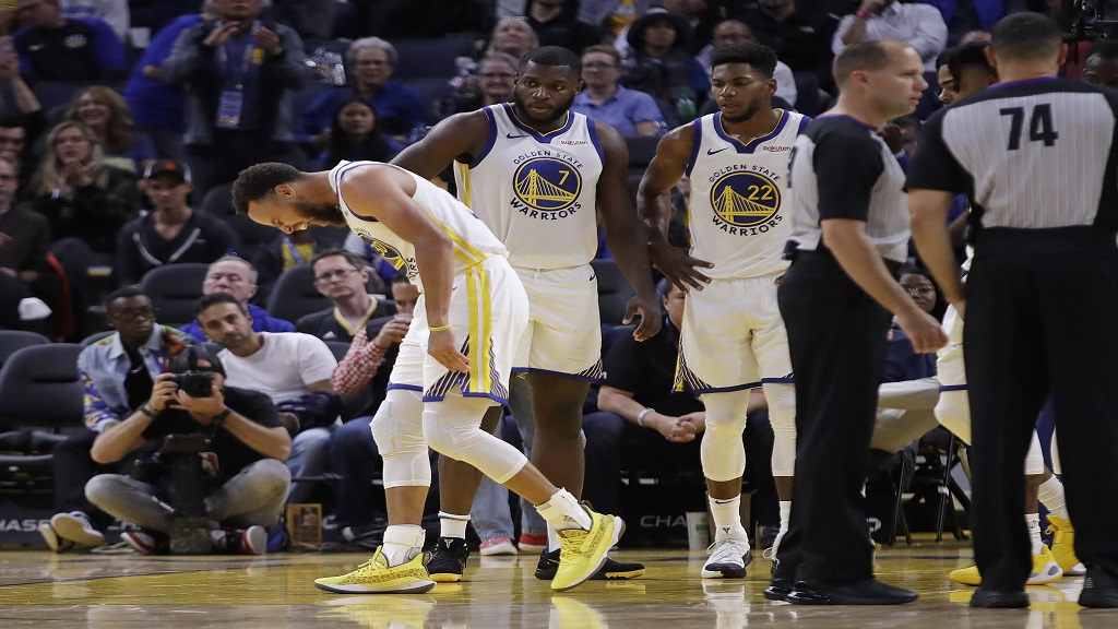 Golden State Warriors' Stephen Curry, left, grimaces after Phoenix Suns' Aron Baynes fell onto him during the second half of an NBA basketball game Wednesday, Oct. 30, 2019, in San Francisco. Curry left the game.  (AP Photo/Ben Margot).