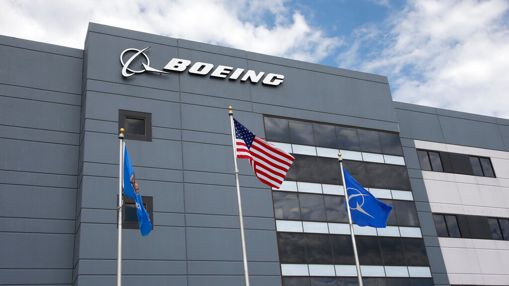 FILE - In this May 14, 2019, file photo flags fly outside the main building of The Boeing Company's Oklahoma City facility in Oklahoma City. Boeing Co. reports financial earns on October 23. (AP Photo/Sue Ogrocki, File)