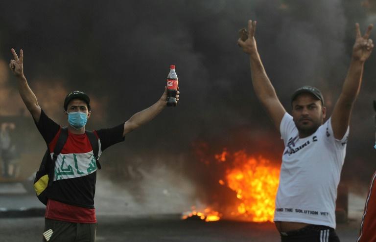 Des manifestants irakiens font le signe de la victoire lors de manifestations antigouvernementales à Bagdad, le 26 octobre 2019