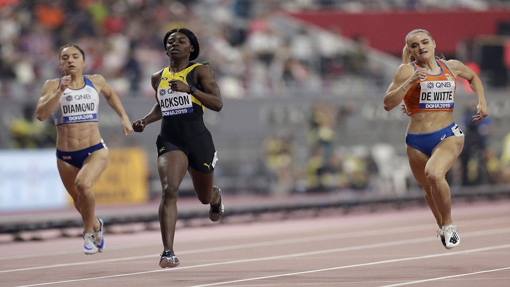 Emily Diamond of Great Britain, Shericka Jackson of Jamaica and Lisanne De Witte of the Netherlands race in a women's 400m heat at the World Athletics Championships in Doha, Qatar, Monday, Sept. 30, 2019. (AP Photo/Petr David Josek)