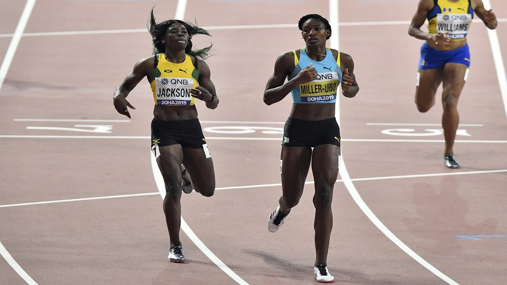 Shericka Jackson, of Jamaica, left, and Shaunae Miller-Uibo, of Bahamas, cross the finish line of the women's 400m semifinals at the World Athletics Championships in Doha, Qatar, Tuesday, Oct. 1, 2019. (AP Photo/Martin Meissner).