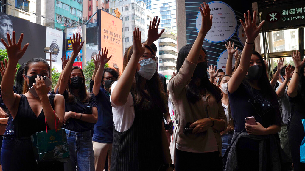 Protesters wear masks and hold up their hands to represent the protesters' five demands in Hong Kong on Friday, Oct. 4, 2019. (AP Photo/Vincent Yu)