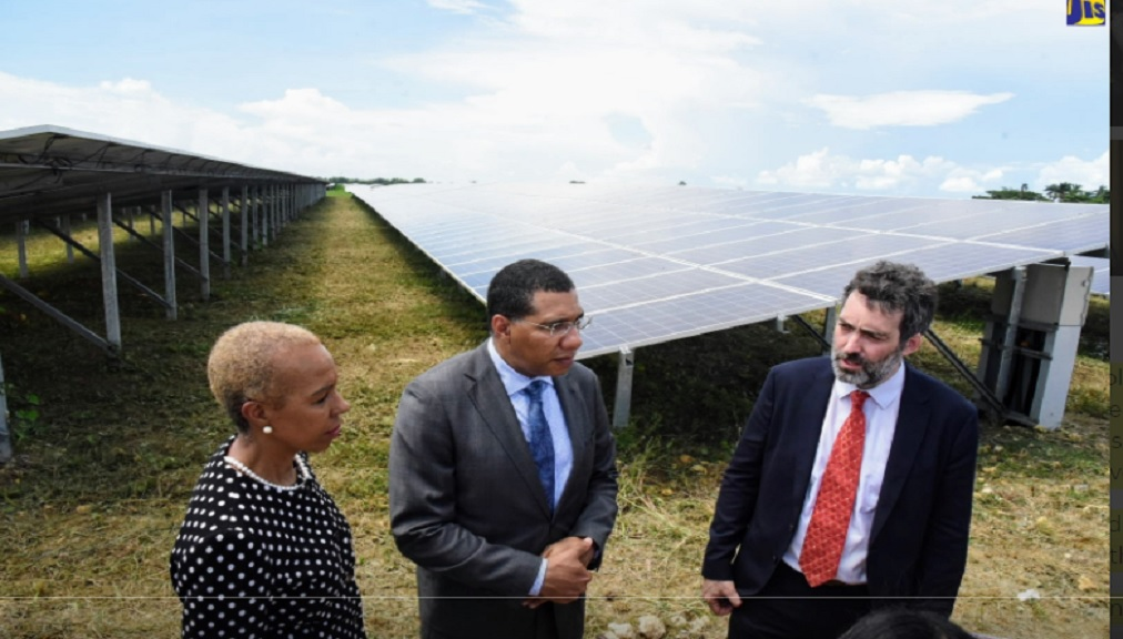 Prime Minister,  Andrew Holness (centre), listens to Deputy Chief Executive Officer (CEO) of Paradise Park Solar Farm in Westmoreland, Romain Desrousseaux, during a tour on October 2. At left is Minister of Science, Energy and Technology,Fayval Williams.