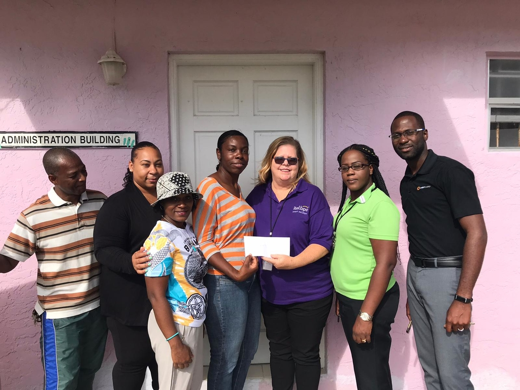 itelbpo Operations Manager Dolly Sitek (3rd right) hands over a cheque valued US$15,000 Columbus House for Boys and Girls Home Administrator Eleanor Williams (centre) in aid of rebuilding efforts in the aftermath of Hurricane Dorian.