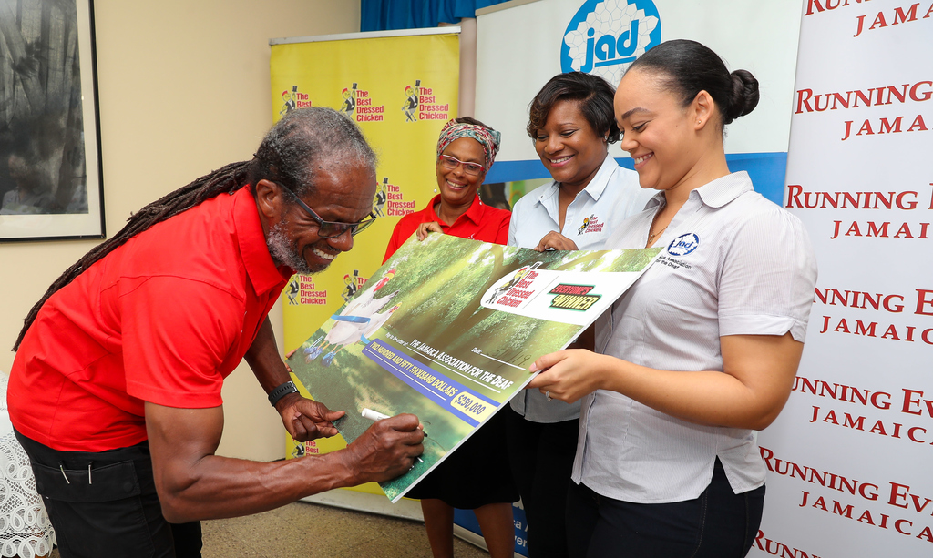 Running Events Jamaica Director, Alfred 'Frano' Francis signs the symbolic cheque of S250,000 to the Jamaica Association for the Deaf (JAD), part proceeds raised from the Everyone's A Winner/The Best Dressed Chicken 5K & 10K race event. Looking on are from (left), Dianne Ellis, Director, Running Events Jamaica; Lorraine Kemble, Brand Manager, The Best Dressed Chicken and Kimberley Sherlock Marriott-Blake, Executive Director of the JAD.